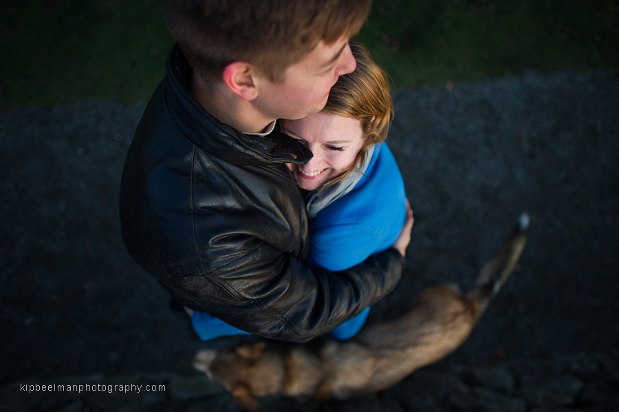 An engaged couple light heartedly embrace while their dog roams at their feet while at Discovery Park in Seattle