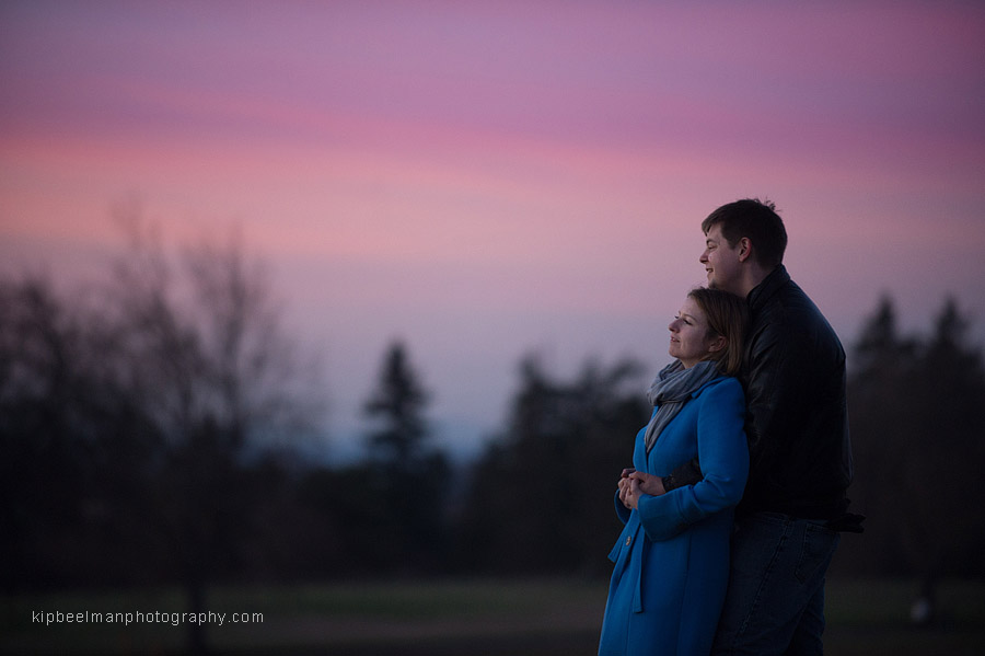 A couple stand together amid purple, pink skies during their engagement photography session in Seattle's Discovery Park
