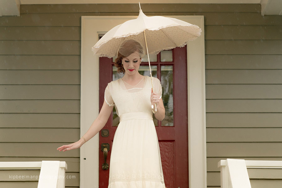 A bride departs her getting ready location and descends steps in her unique family heirloom wedding gown holding a vintage parasol from Bella Umbrella en route to her first look for her Golden Gardens Bathhouse wedding