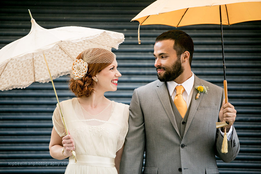 A bride and groom pose side by side while looking at each other for their Golden Gardens Bathhouse wedding holding vintage parasols from Bella Umbrella