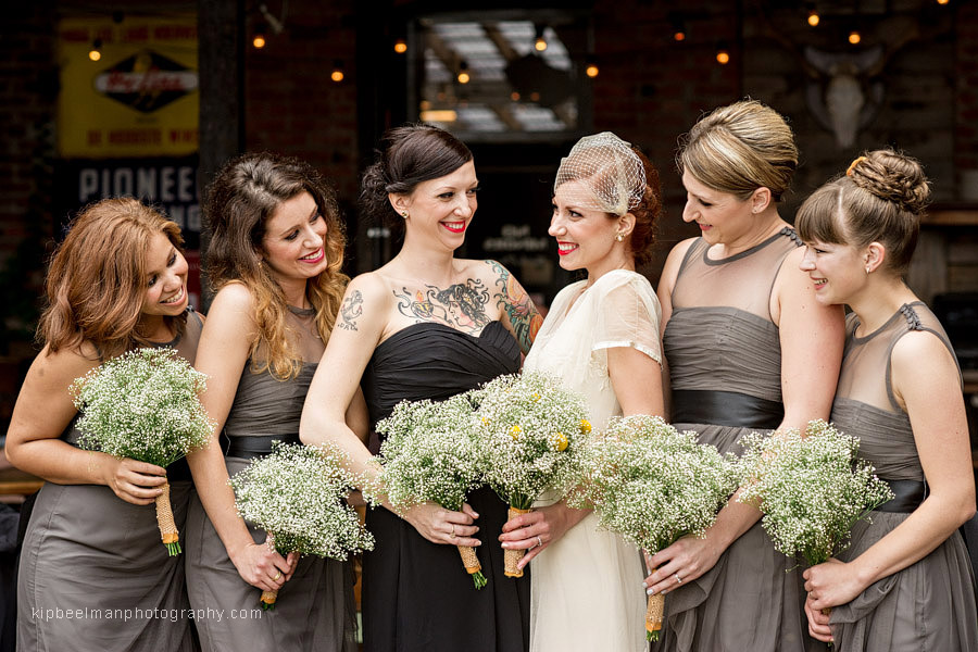 A bride and her bridesmaids interact casually with big smiles on the patio of King's Hardware in Ballard before their Golden Gardens Bathhouse wedding
