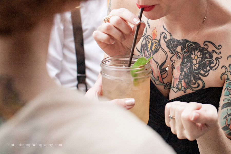 The maid of honor for a Golden Gardens Bathhouse wedding sips a mojito at King's Hardware in Ballard while her elaborate chest tattoo is highlighted