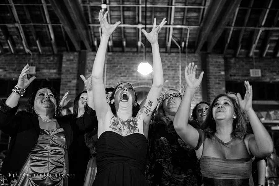 Mouths are agape and arms outstretched in an effort to catch the tossed bouquet at a Golden Gardens Bathhouse Wedding