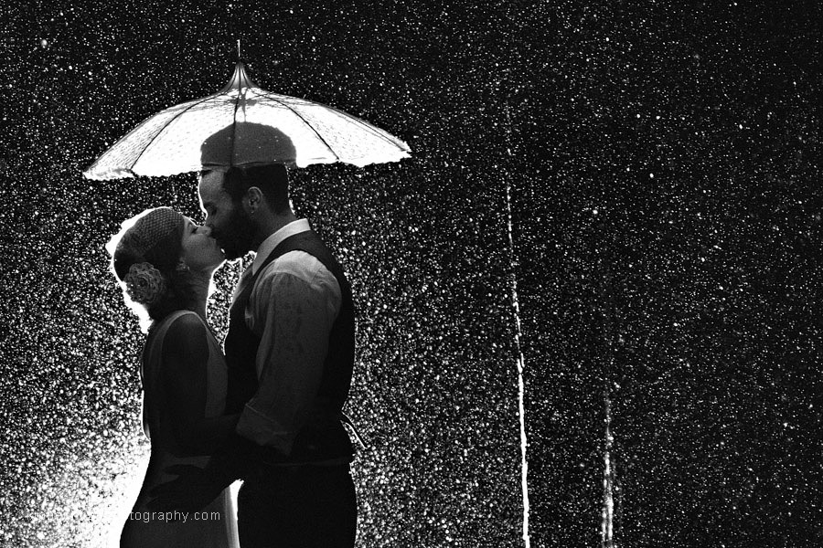 A Golden Gardens Bathhouse wedding couple are photographed under a vintage parasol from Bella Umbrella at night with a backlight to highlight the torrent of rain falling around them