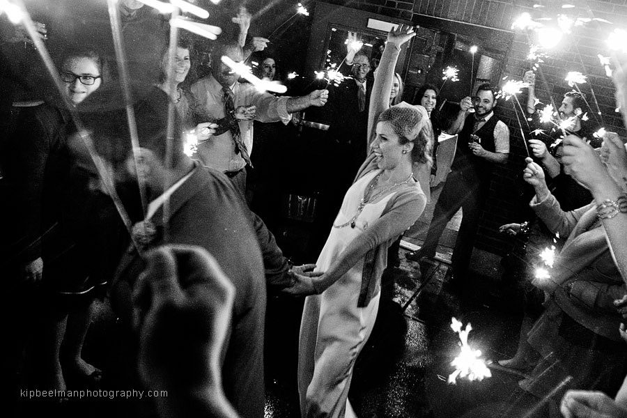 A groom tows his bride during their Golden Gardens Bathhouse wedding sparkler send off in the rain