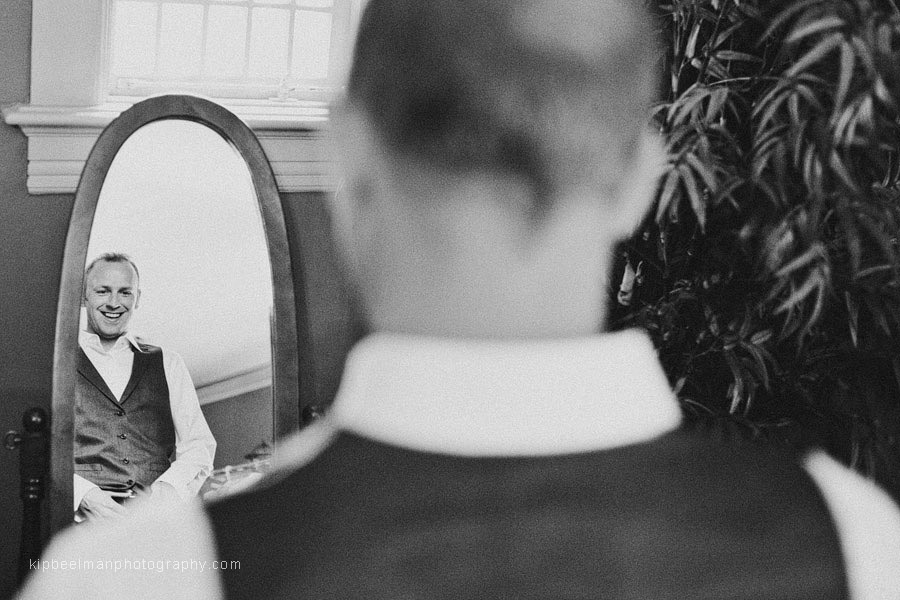 A groom readies himself in front of a mirror for his Glover Mansion wedding