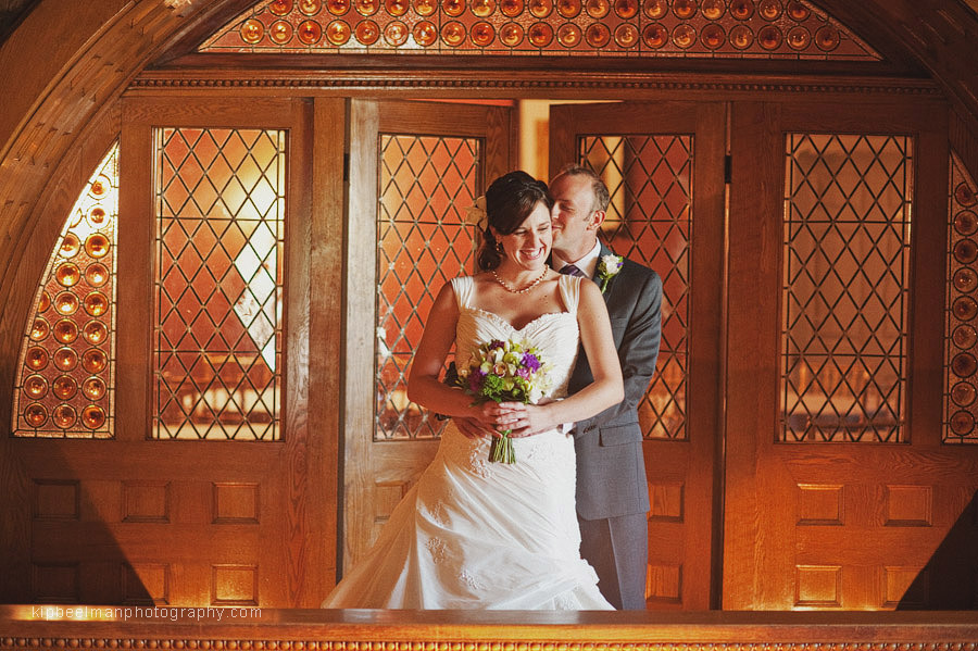 A bride and groom share a snuggle on a golden balcony as part of their Glover Mansion wedding celebration