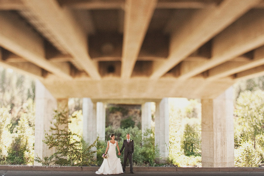 A bride and groom hold hands underneath an overpass while on a portrait stroll as part of their Glover Mansion wedding