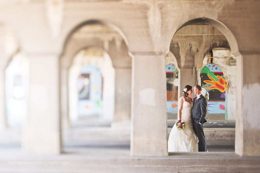 A bride and groom pose under Spokane's downtown railroad tracks on a break from their Glover Mansion wedding