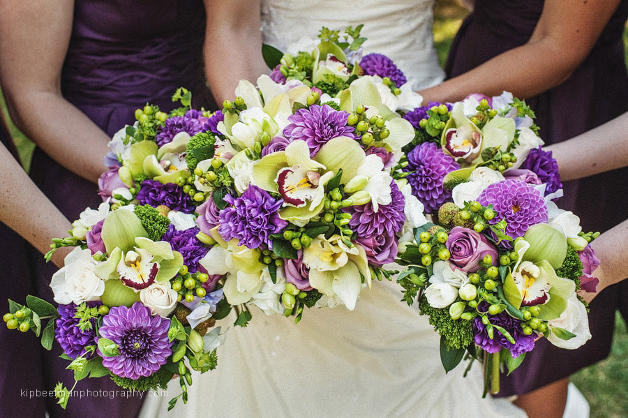 Beautiful purple flowers mix with orchids and roses as a bride and bridesmaids present their bouquets for a Glover Mansion wedding