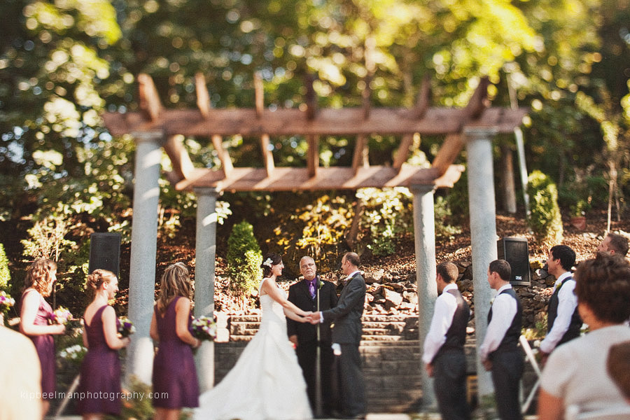 A view of the 3 bridesmaids in purple and groomsmen in vests flanking the bride and groom as they stand under an arbor at their Glover Mansion wedding