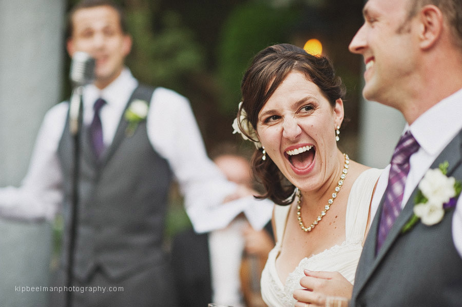 A bride cracks up while looking at her husband while the best man is sharing some words in the background during a Glover mansion wedding ceremony