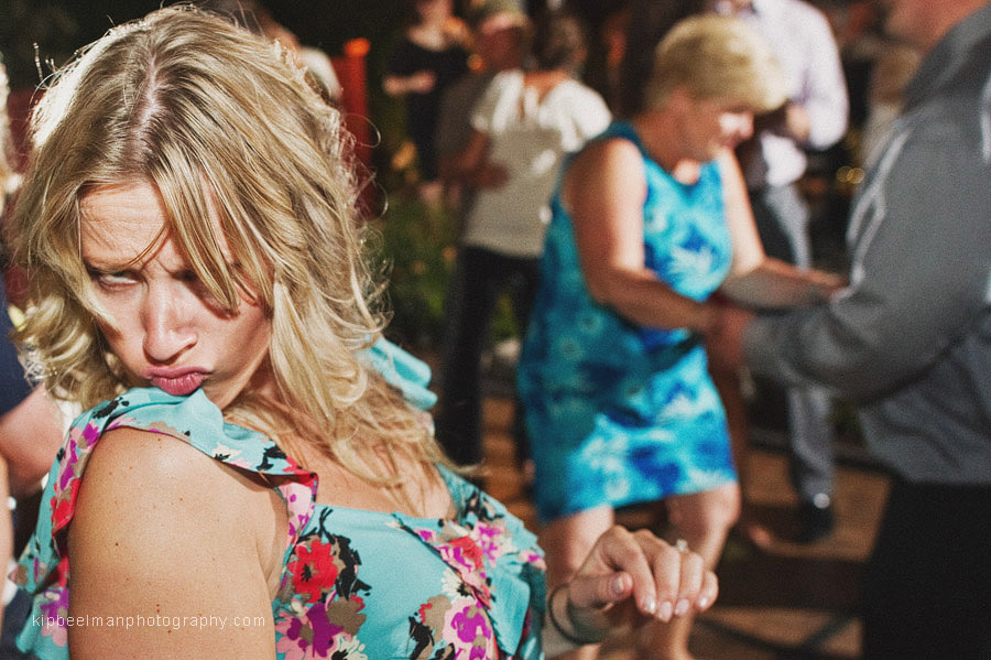 A 20-something blonde is giving saucy duck lips in a floral dress while on the dance floor of a Glover Mansion wedding