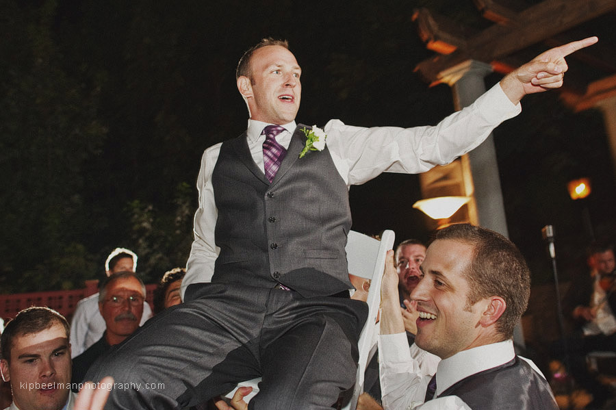 A groom is hoisted above the dance floor of his Glover Mansion wedding by the groomsmen