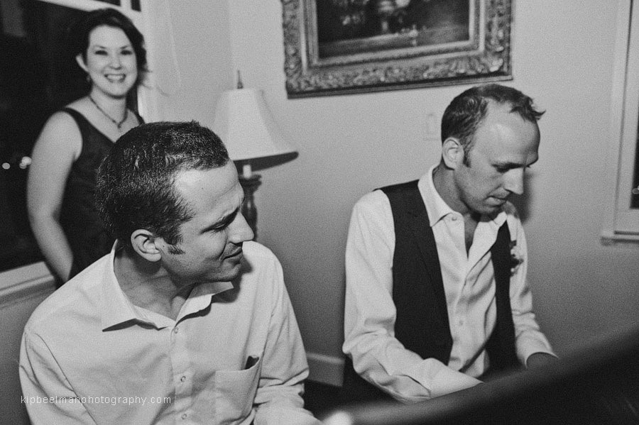A groom entertains guests with the piano and singing in the Presidential Suite of the Davenport Hotel after his Glover Mansion wedding