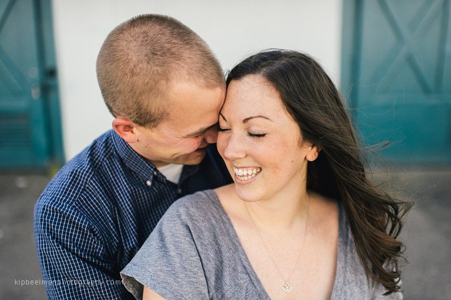 A couple snuggle in front of a net shed during their Fishermens Terminal engagement session