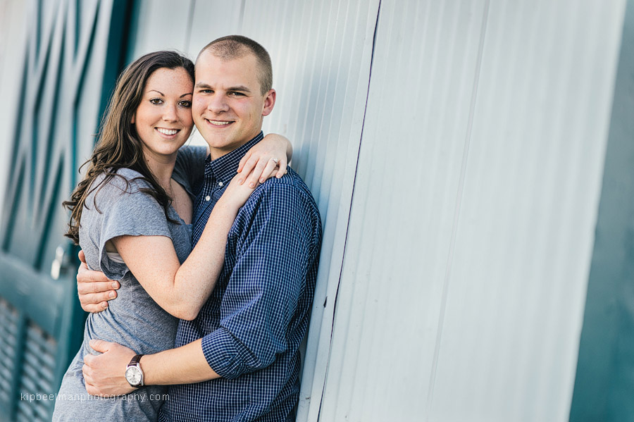 A Fishermens Terminal engagement session sees a couple posing together against a net shed wall