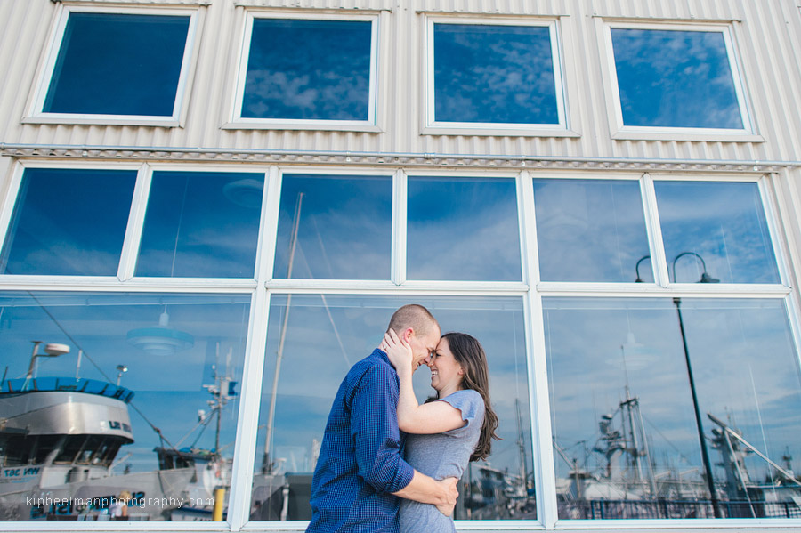 A smiling couple pose with their heads together in embrace in front of a building reflecting blue sky and boats in the windows during their Fishermens Terminal engagement session