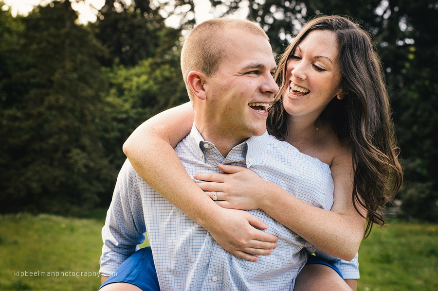A smiling guy give a smiling girl a piggy back ride in Discovery Park after their Fishermens Terminal engagement session