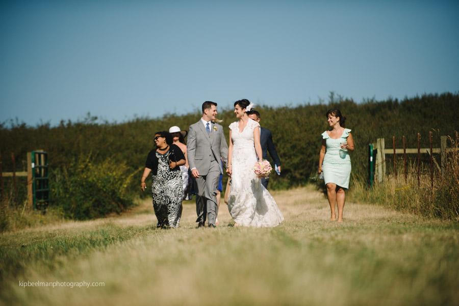 Bride and Groom walk through meadow