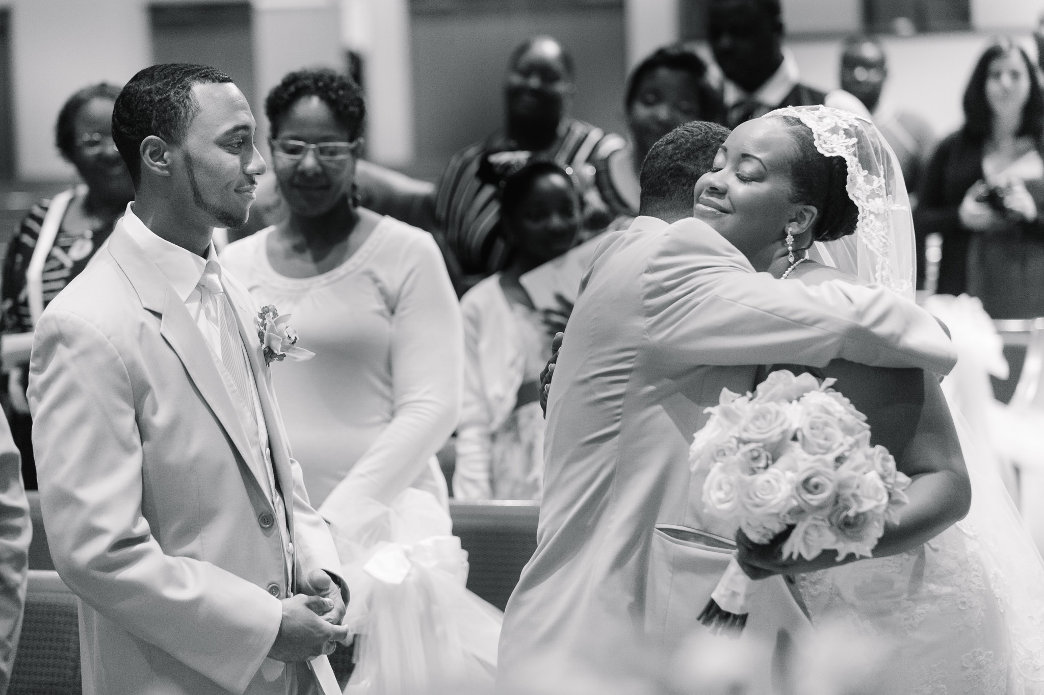 A father hugs his daughter as the groom looks on at this Buffalo wedding ceremony