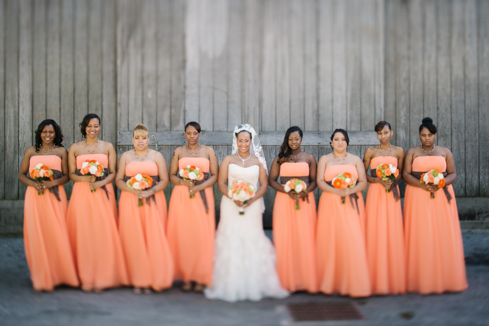 The Buffalo wedding bridal party post for a portrait featuring their peach dresses